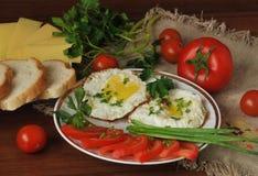Τηγανισμένα αυγά, ώριμες ντομάτες κερασιών και φρέσκα χορτάρια Τυρί και άσπρο ψωμί Στοκ φωτογραφίες με δικαίωμα ελεύθερης χρήσης