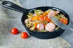 Τηγανισμένα λαχανικά με το τεμαχισμένο λουκάνικο σε ένα skillet χυτοσιδήρου Στοκ φωτογραφία με δικαίωμα ελεύθερης χρήσης