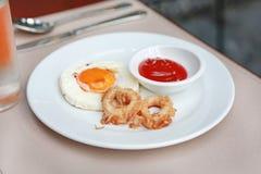 Τηγανισμένα δαχτυλίδια calamari και τηγανισμένο αυγό με τη σάλτσα ντοματών στο πιάτο στοκ φωτογραφία με δικαίωμα ελεύθερης χρήσης