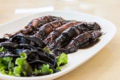 Τηγανισμένα καλαμάρι και ζυμαρικά με τη μαύρη σάλτσα στο πιάτο Στοκ Εικόνες