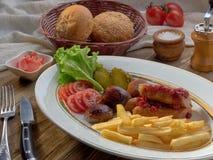 Τηγανισμένα λουκάνικα με τις τηγανιτές πατάτες, τη σαλάτα και τα μανιτάρια στοκ εικόνα με δικαίωμα ελεύθερης χρήσης