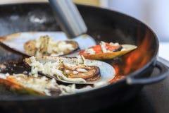 Τηγανισμένα μύδια με τα κομμάτια του τυριού σε ένα τηγανίζοντας τηγάνι Στοκ εικόνα με δικαίωμα ελεύθερης χρήσης