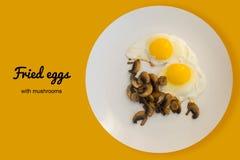 Τηγανισμένα οργανικά αυγά με τα μανιτάρια σε ένα άσπρο πιάτο Στοκ φωτογραφία με δικαίωμα ελεύθερης χρήσης