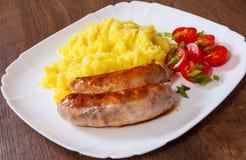 Τηγανισμένα λουκάνικα κρέατος με την πολτοποιηίδα σαλάτα πατατών και λαχανικών Στοκ Φωτογραφίες