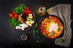 Τηγανισμένα πρόγευμα αυγά με τα λαχανικά - shakshuka σε ένα τηγανίζοντας τηγάνι Στοκ Φωτογραφία