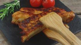 Τηγανισμένα πλευρά χοιρινού κρέατος που τίθενται σε έναν πίνακα μερίδας σε αργή κίνηση απόθεμα βίντεο
