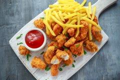 Τηγανισμένα τριζάτα ψήγματα κοτόπουλου με τις τηγανιτές πατάτες και κέτσαπ στο λευκό πίνακα Στοκ φωτογραφία με δικαίωμα ελεύθερης χρήσης