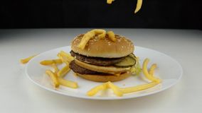 Τηγανισμένα τσιπ πατατών που αφορούν κάτω το χάμπουργκερ, σε αργή κίνηση, γρήγορο φαγητό, έννοια άχρηστου φαγητού απόθεμα βίντεο