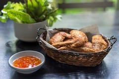 Τηγανισμένα φτερά κοτόπουλου στο καλάθι, και γλυκόπικρη σάλτσα με το τσίλι για την εμβύθιση κοτόπουλου στοκ εικόνες