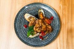 Τηγανισμένα φτερά με τα μύδια σε ένα μαύρο πιάτο στοκ φωτογραφία με δικαίωμα ελεύθερης χρήσης