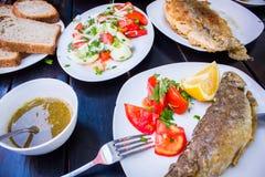 Τηγανισμένα ψάρια με τα φρέσκα χορτάρια και το λεμόνι στοκ εικόνες