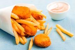Τηγανισμένα ψήγματα ψαριών με τις τηγανιτές πατάτες Στοκ Εικόνες