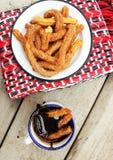 Τηγανισμένα churros με τη ζάχαρη cinnamom και τη σάλτσα σοκολάτας Στοκ Εικόνα