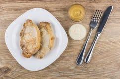 Τηγανισμένα cutlets χοιρινού κρέατος στο πιάτο, μουστάρδα, χρένο, δίκρανο και knif Στοκ φωτογραφία με δικαίωμα ελεύθερης χρήσης