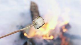 Τηγανισμένα marshmallows σε μια φωτιά το χειμώνα κοντά επάνω φιλμ μικρού μήκους