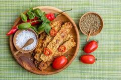 Τηγανισμένα tempeh, τα πιπέρια τσίλι, οι φρέσκες ντομάτες κερασιών, το μίγμα των χορταριών και η θάλασσα αλατίζουν στα ξύλινα δοχ Στοκ Εικόνες