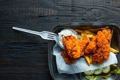 Τηγανισμένες κοτόπουλο και τηγανιτές πατάτες και σε ένα take-$l*away εμπορευματοκιβώτιο στο ξύλινο υπόβαθρο Παράδοση τροφίμων και στοκ εικόνα με δικαίωμα ελεύθερης χρήσης