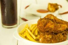 Τηγανισμένες κοτόπουλο και τηγανιτές πατάτες στον πίνακα στοκ φωτογραφία