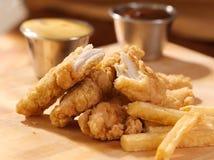 Τηγανισμένες λουρίδες κοτόπουλου με τις τηγανιτές πατάτες και τη σάλτσα. Στοκ Φωτογραφίες