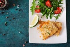 Τηγανισμένες λωρίδες άσπρων ψαριών και σαλάτα ντοματών με το arugula Στοκ εικόνα με δικαίωμα ελεύθερης χρήσης