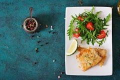 Τηγανισμένες λωρίδες άσπρων ψαριών και σαλάτα ντοματών με το arugula Στοκ Φωτογραφία