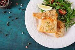 Τηγανισμένες λωρίδες άσπρων ψαριών και σαλάτα ντοματών με το arugula Στοκ Φωτογραφίες