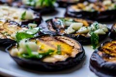 Τηγανισμένες μπλε μελιτζάνες με το φρέσκο σκόρδο και πράσινα σε ένα στρογγυλό άσπρο πιάτο, καυτός και ορεκτικός Σπιτικό μαγείρεμα στοκ εικόνες