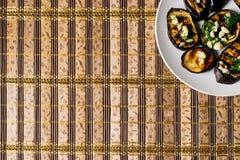 Τηγανισμένες μπλε μελιτζάνες με το φρέσκο σκόρδο και πράσινα σε ένα στρογγυλό άσπρο πιάτο, καυτός και ορεκτικός Σπιτικό μαγείρεμα στοκ φωτογραφία