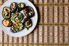 Τηγανισμένες μπλε μελιτζάνες με το φρέσκο σκόρδο και πράσινα σε ένα στρογγυλό άσπρο πιάτο, καυτός και ορεκτικός Σπιτικό μαγείρεμα στοκ εικόνα με δικαίωμα ελεύθερης χρήσης
