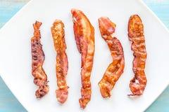 Τηγανισμένες λουρίδες μπέϊκον στο τετραγωνικό πιάτο στοκ εικόνες