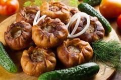 Τηγανισμένες πίτες κρέατος belyash με τα λαχανικά στον ξύλινο πίνακα στοκ εικόνες με δικαίωμα ελεύθερης χρήσης