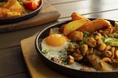 Τηγανισμένες πατάτες με τα μανιτάρια και ένα τηγανισμένο αυγό Στοκ Φωτογραφία