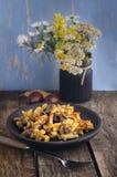 Τηγανισμένες πατάτες με τα μανιτάρια σε ένα σκοτεινό κεραμικό πιάτο με έναν παλαιό ξύλινο πίνακα Στοκ εικόνες με δικαίωμα ελεύθερης χρήσης