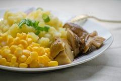Τηγανισμένες πατάτες με τα cepes και καλαμπόκι σε ένα πιάτο στον πίνακα Τηγανισμένες πατάτες με τα παστωμένα μανιτάρια και το καλ στοκ φωτογραφία