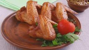 Τηγανισμένες πτώσεις φτερών κοτόπουλου σε ένα σε αργή κίνηση μήκος σε πόδηα πιάτων φιλμ μικρού μήκους