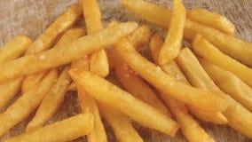 Τηγανισμένες τηγανιτές πατάτες πατάτες που ψεκάζονται με το αλατισμένο σε αργή κίνηση βίντεο μήκους σε πόδηα απόθεμα βίντεο