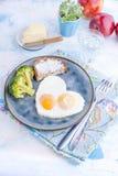 τηγανισμένη μορφή καρδιά α&upsilon Σε ένα σκοτεινό πιάτο με το μπλε φλυτζάνι μπρόκολου και φρυγανιάς με το τσάι, μήλα, βούτυρο γι Στοκ Εικόνες