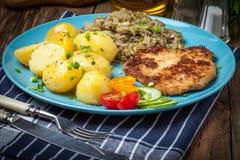 Τηγανισμένη μπριζόλα χοιρινού κρέατος, ψημένες πατάτες και τηγανισμένο νέο λάχανο Στοκ Φωτογραφίες