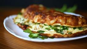 Τηγανισμένη ομελέτα με το κουνουπίδι και πράσινα σε ένα πιάτο απόθεμα βίντεο