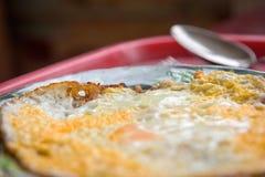 Τηγανισμένη ομελέτα σε ένα πιάτο και ένα κουτάλι σπιτικά στην εκλεκτική εστίαση δίσκων Στοκ Φωτογραφίες