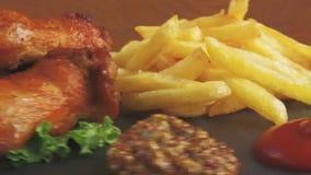 Τηγανισμένη σάλτσα τηγανιτών πατατών φτερών κοτόπουλου στις στροφές πετρών πιάτων απόθεμα βίντεο