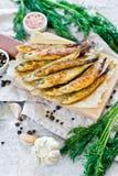 Τηγανισμένη τήξη σε έναν ξύλινο τεμαχίζοντας πίνακα, έναν άνηθο, ένα ρόδινο αλάτι, ένα πιπέρι και ένα σκόρδο Γκρίζο υπόβαθρο, τοπ στοκ φωτογραφία
