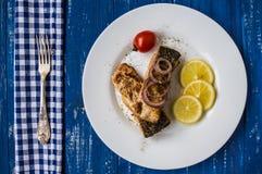 Τηγανισμένη λωρίδα ψαριών με το λεμόνι και ντομάτες σε ένα άσπρο πιάτο Ξύλινο μπλε υπόβαθρο Τοπ όψη Κινηματογράφηση σε πρώτο πλάν Στοκ φωτογραφία με δικαίωμα ελεύθερης χρήσης