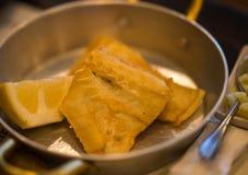 Τηγανισμένος βακαλάος στις παν και πολτοποιηίδες πατάτες μετάλλων στο πιάτο Στοκ Φωτογραφίες