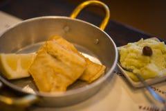 Τηγανισμένος βακαλάος στις παν και πολτοποιηίδες πατάτες μετάλλων στο πιάτο Στοκ φωτογραφία με δικαίωμα ελεύθερης χρήσης