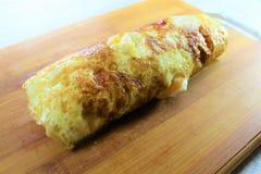 Τηγανισμένος ρόλος ομελετών αυγών που γεμίζουν με το τυρί και τα κολοκύθια με το άσπρο ξύλινο υπόβαθρο στοκ εικόνα με δικαίωμα ελεύθερης χρήσης