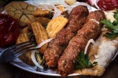 Τηγανισμένος kebab kebab με ψημένα στη σχάρα τη λαχανικά σάλτσα, το κρεμμύδι και τα καρυκεύματα σχάρα Στοκ εικόνες με δικαίωμα ελεύθερης χρήσης