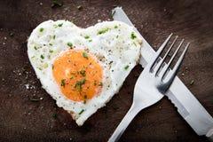 Τηγανισμένο αυγό με τη μορφή καρδιών και μαχαιροπήρουνα στο ξύλινο υπόβαθρο Στοκ Εικόνα