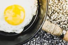 Τηγανισμένο αυγό σε ένα τηγανίζοντας τηγάνι στο γκρίζο αμμοχάλικο στοκ φωτογραφία