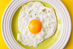 Τηγανισμένο αυγό στο άσπρος-πράσινο πιάτο στο κίτρινο υπόβαθρο Στοκ εικόνα με δικαίωμα ελεύθερης χρήσης